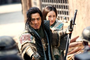 Xin Qing (Mika Wang), back, and Huo An (Jackie Chan) in DRAGON BLADE. Photo credit: Lionsgate Premiere, press site